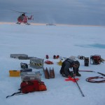 Dr. Michelle Johnston assembling ice drilling gear in Nares Strait with Greenland on the horizon. The Canadian Coast Guard Ship Henry Larsen in the background with its helicopter hovering.