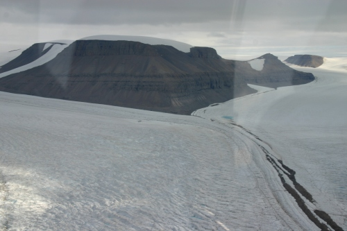 The merging of Sigurd Berg and Hubert Glaciers which discharge into Petermann Gletscher on its eastern wall. The view is landward towards the north-east as the helicopter flies in from Petermann. [Credit: Barbara O'Connell, Canadian Coast Guard]