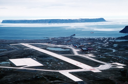 Thule AFB with its airport, pier, and ice-covered ocean in the summer. The island is Saunders Island. The ship is most likely the CCGS Henry Larsen in 2007. [Credit: Unknown]