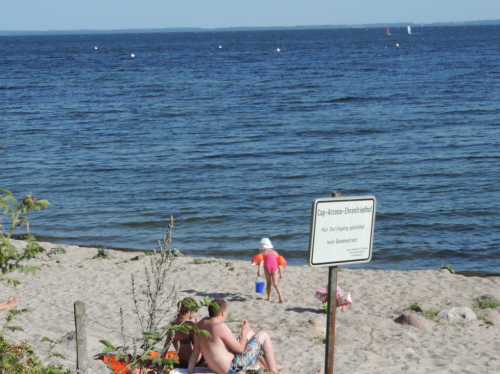 "A family on a beach of Neustadt in Holstein July-24, 2013. The view is across the Luebecker Bucht. The posted sign reads ""Cap Arcona Ehrenfriedhof. Nur Durchang gestatted. Kein Badebetrieb."" It states that this is cemetery, walk-through is allowed, but no other beach activity."