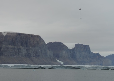 Photo of helicopter delivering cargo from the finished ice camp back to the ship on 23 Aug. 2015.