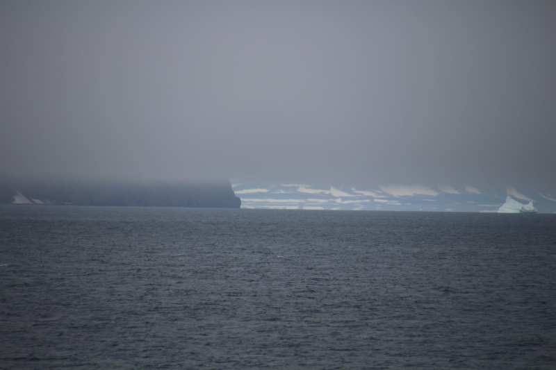 Kap Brewster in the clouds (foreground) at the southern entrance to Scoresby Sund. View is to the north-west into the entrance of the fjord. In the background the northern shores are visible behind the iceberg. [Photo by Dragonfly Leathrum]