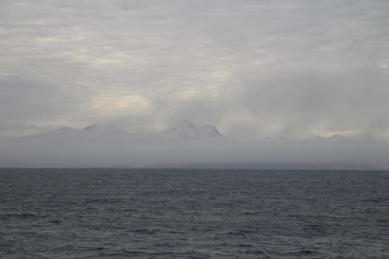 Coastal Greenland in the fog as we approach the entrance to Scoresby Sund on Aug. 20, 2018. [Photo by Dragonfly Leathrum]